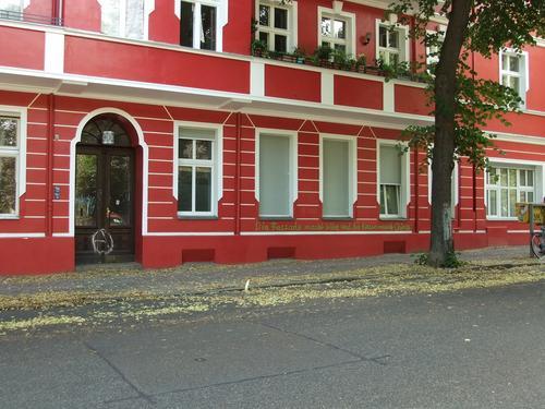 Ein rotes Haus mit grünem Graffiti in Neukölln